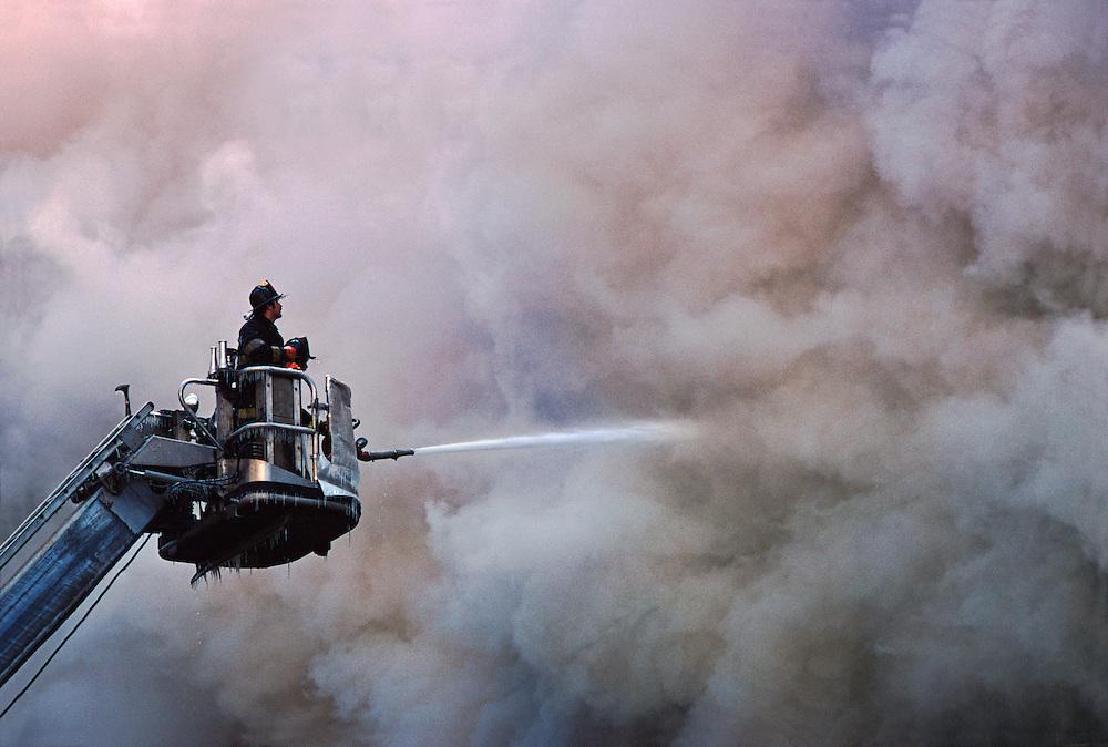 Firemen On Ladder Spraying Water Into Thick Smoke, Manhattan, New York City, New York, USA