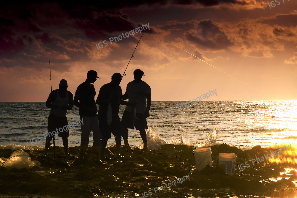 Silhouetted Fisherman displaying their catch at sunrise in Boca Raton Florida