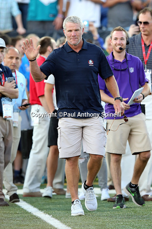 Former Green Bay Packers quarterback Brett Favre waves to fans while being announced over the public address system as he walks onto the field as a new member of the Pro Football Hall of Fame before the 2016 NFL Pro Football Hall of Fame preseason football game against the Indianapolis Colts on Sunday, Aug. 7, 2016 in Canton, Ohio. The game was canceled for player safety reasons due to the condition of the paint on the turf field. (©Paul Anthony Spinelli)