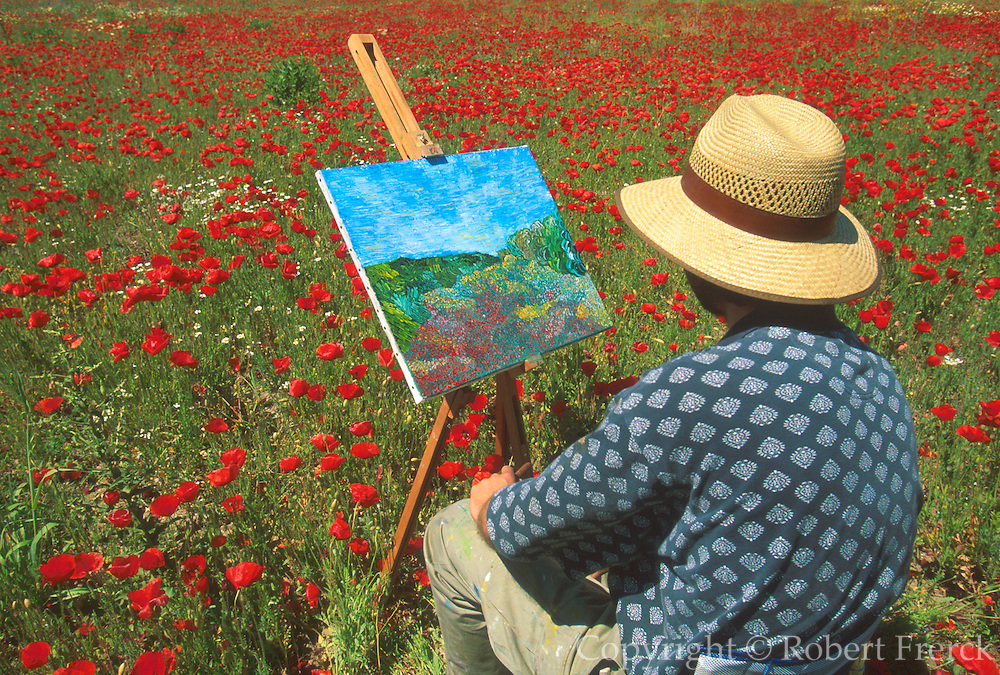 SPAIN, ANDALUSIA, COSTA DEL SOL artist painting a landscape surrounded by a sea of wildflowers near Estepona
