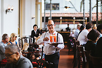 A waiter serves Singapore Slings at the Raffles Hotel in Singapore.