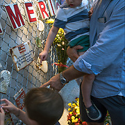 Father and two son hang tile on fence.<br /> <br /> Special candlelight remembrance 7pm on 9/11/2015, Mulry Square @ Greenwich Avenue &amp; 7th Avenue South fo Tiles For America.<br /> <br /> Tiles with messages of inspiration and remembrance.