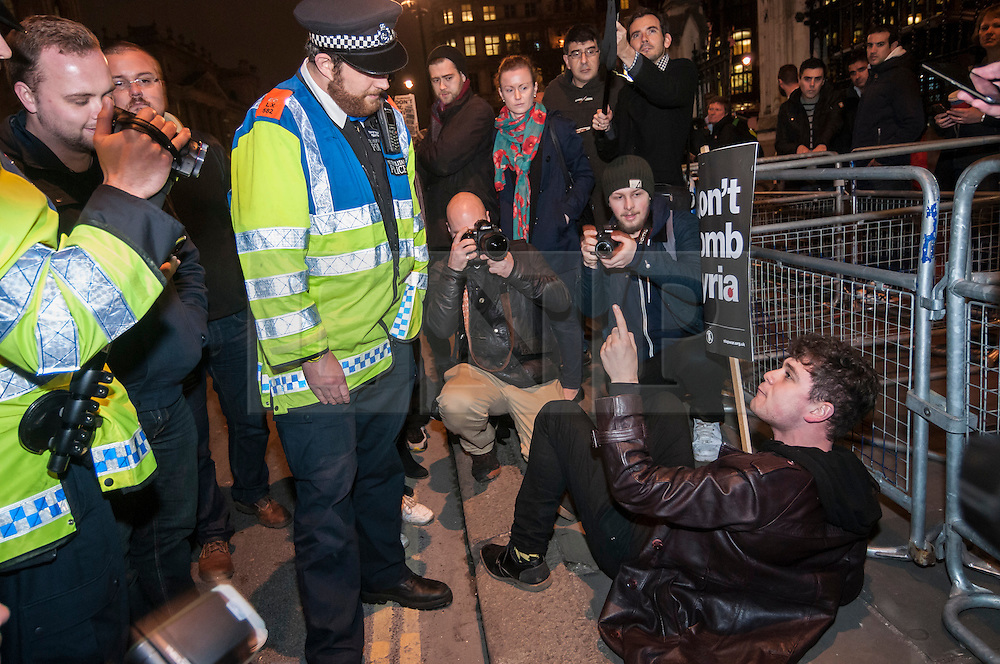 """© Licensed to London News Pictures. 02/12/2015. London, UK. Police requests a protestor to move out of the road to allow traffic to pass.  As MP's decide in Parliament whether to vote for the UK to commence air strikes in Syria, thousands of anti-war protestors stage a """"die in"""" in Parliament Square urging MPs to vote against military action.  Photo credit : Stephen Chung/LNP"""