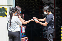 © Licensed to London News Pictures. 15/06/2020. London, UK. Shoppers in Kingston, South West London are given hand gel as non essential shops are given the green light to open in England after 3 months of being closed due to the coronavirus pandemic. Also commuters are told to wear face masks from Monday while travelling on Public transport. Photo credit: Alex Lentati/LNP
