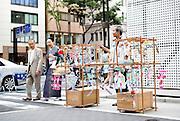 Yoshitomo Sasaki carries a wooden frame onto which have been hung several dozen Edo furin, or glass wind chimes, which he sells on the streets of chic Ginza district in Tokyo, Japan. The chimes, which date back more than 200 years in Japan, were traditionally carried around town dangling from  bamboo poles by sellers. Sasaki is one of a few people who continue this trend.A couple walks past Edo furin, or glass wind chimes, displayed on a wooden frame by seller Yoshitomo Sasaki in the chic Ginza district in Tokyo, Japan. The chimes, which date back more than 300 years in Japan, were traditionally carried around town dangling from  bamboo poles by sellers. Sasaki is one of a few people who continue this trend.