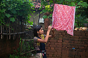 Tabasum Khatun, 14, is drying the cloth used to filter water from the well, while standing in the courtyard of her home in Algunda village, pop. 1000, Giridih District, rural Jharkhand, India.