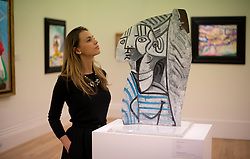 © Licensed to London News Pictures. 12/04/2013. London, UK. Gallery assistant poses next to Pablo Picasso's 'Sylvette' artwork with an estimated value of between 12 - 18 million USD for the upcoming New York auctions. Highlights from Sotheby's New York auctions of Impressionist and Modern Art and Contemporary Art will be exhibited to the public from 12-16 April at  Sotheby's London New Bond Street galleries. Photo credit : Peter Kollanyi/LNP