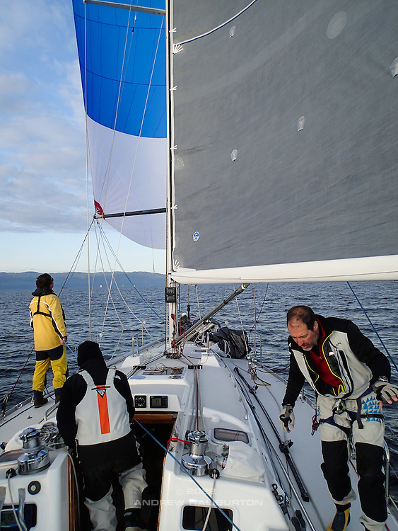 Temperature dive after sunset busies the crew aboard J/46 Riva in the Strait of Juan de Fuca.  2014 Swiftsure International Yacht Race, Victoria, British Columbia, Canada.  Olympus Tough TG-1.