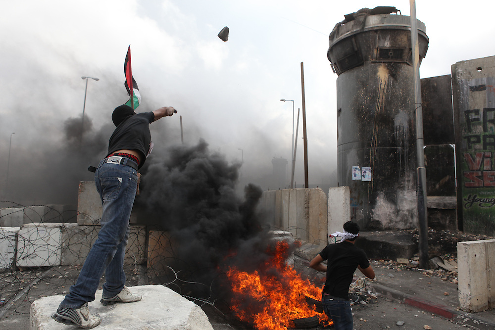 Masked Palestinian protesters hurl stones at Israeli security forces, during clashes following Friday noon prayers at the Qalandia checkpoint between Ramallah and Jerusalem, Friday, Sept. 23, 2011/ Gilad Kavalerchik