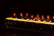 Brooklyn, NY - 11 December 2019. A performance of In Many Hands in BAM's Fishman Space, by Kate McIntosh in collaboration with Arantxa Martinez and Josh Rutter; sound design by John Avery; lighting design by Joëlle Reyms. The piece involves participants sitting at 3 long, narrow tables, with facilitators at each end, and either passing along objects or repeating hand movements in the manner set by a facilitator.