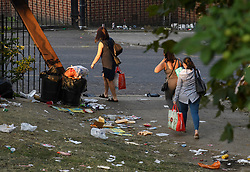© Licensed to London News Pictures. 27/08/2019. London, UK. Members of the public walk through rubbish and debris strewn across a public park in Notting Hill, west London, in the aftermath of the 2019 Notting Hill carnival. The two day event is the second largest street festival in the world after the Rio Carnival in Brazil, attracting over 1 million people to the streets of West London. Photo credit: Ben Cawthra/LNP