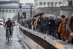 © Licensed to London News Pictures. 15/01/2020. London, UK. Commuters head to work along Waterloo Bridge this morning. After last nights storms a gloomy start for commuters at Waterloo this morning as more rain and high winds are expect for Thursday 16/01/2020. Photo credit: Alex Lentati/LNP