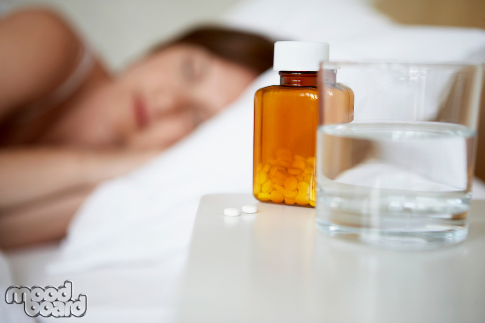 Sick woman in bed by pills on bedside table focus on foreground