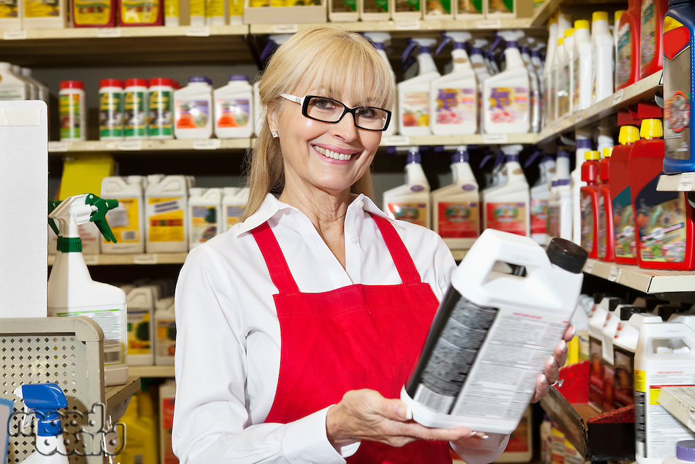 Portrait of a senior woman holding can in retail store