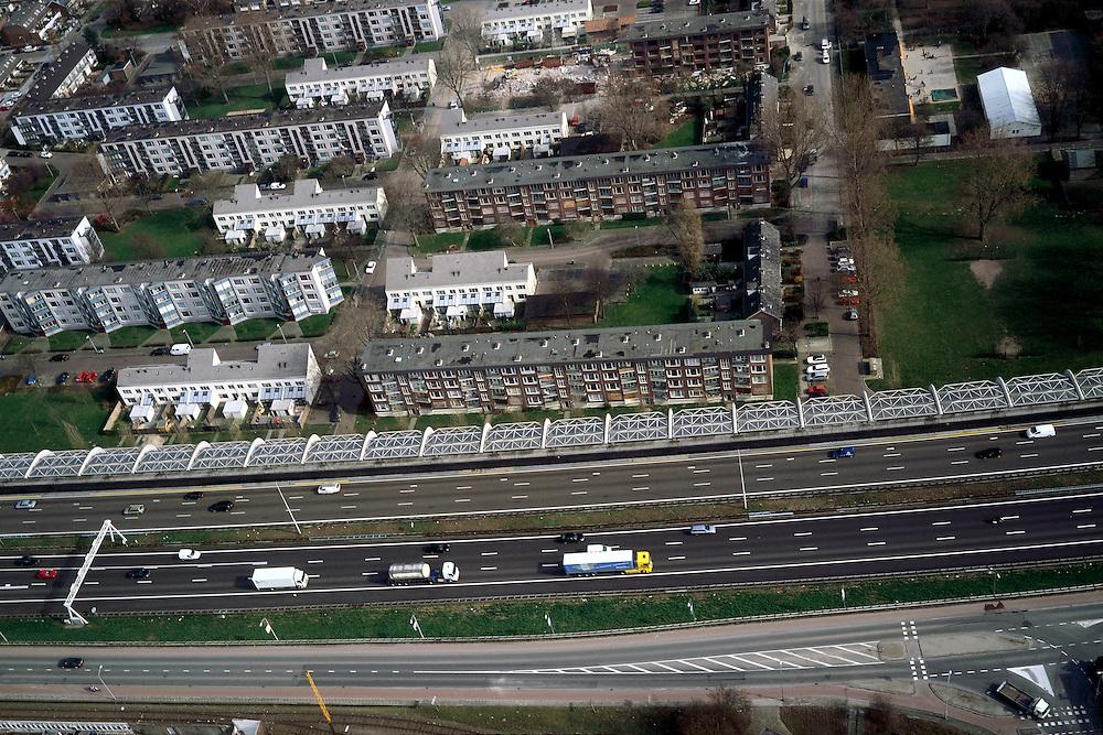 Nederland, Zuid-Holland, Dordrecht, 08-03-2002; de zeer verkeersintensieve autosnelweg A16 (Rotterdam -Breda) loopt direct langs de woonwijk ' Wielwijk'; om geluidsoverlast tegen te gaan is een enorm, half gebogen, geluidsscherm gebouwd,  geluidswal met gebogen betonnen spanten en glazen dak; de jaren zestig woonwijk wordt gedeeltelijk gesloopt / gerenoveerd; milieu verkeer en vervoer volksgezondheid .stadsvernieuwing flats.;<br /> luchtfoto (toeslag), aerial photo (additional fee)<br /> foto /photo Siebe Swart