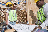 Two construction workers studying blueprints