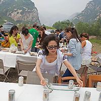 BEIJING, JUNE 24, 2013 : Mitglieder von Li Xiaohua's Elite Club bereiten die Tische fuer ein Picknick in Peking's Natur Reservoir Miyun vor. Li gruendete den Club vor einem Jahr . Mitglieder koennen nur per Einladung beitreten und muessen ein gewisses Einkommen nachweisen koennen.