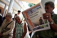 """Un venezolano lee un diario que titula """"Todos a votar tempranito"""" mientras hace cola para votar en el referendo consultivo sobre la reforma constitucional propuesta por el presidente venezolano, Hugo Chávez hoy, domingo 2 de diciembre, en Caracas (Venezuela). (ivan gonzalez)"""