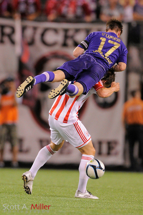 Lions forward Jamie Watson (77) goes airborne over Stoke City Potters midfielder Dean Whitehead (18) as they go for a ball during the Potters 1-0 win at the Florida Citrus Bowl on July 28, 2012 in Orlando, Florida. ..©2012 Scott A. Miller.