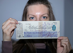Edinburgh auction house, Lyon & Turnbull are offering a cheque for for five pounds and two shillings, paid to the author, DH Lawrence, for three clandestine copies of the controversial novel Lady Chatterley's Lover. The lot is valued at up to £1,200 in the sale that will take place on 11 October 2017.<br /> <br /> Pictured: Laura Kondrataite, Rare Books and Asian Art Administrator holding the cheque