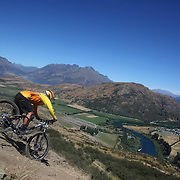 Dario Takada from Christchurch, in action during the New Zealand South Island Downhill Cup Mountain Bike series held on The Remarkables face with a stunning backdrop of the Wakatipu Basin. 150 riders took part in the two day event. Queenstown, Otago, New Zealand. 9th January 2012. Photo Tim Clayton