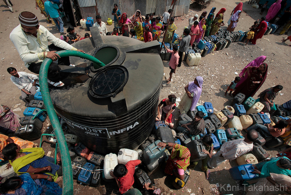 People wait for a water tanker to refill the tank in Mumbai, India on March 19, 2010. Due to the lack of rain in the monsoon season, Mumbai faced one of the worst water shortages in its history and the city government was forced to cut 15 % of its water supply. <br /> (Photo by Kuni Takahashi)