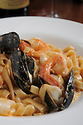 A serving of Penne pasta with Shrimps, mussels and cream sauce