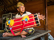 22 JULY 2016 - TENGANAN DUAH TUKAD, BALI, INDONESIA: A drummer performs in the village temple after the pandanus fights in the Tenganan Duah Tukad village on Bali. The ritual Pandanus fights are dedicated to Hindu Lord Indra. Men engage in ritual combat with spiky pandanus leaves and rattan shields. They usually end up leaving bloody scratches on the combatants' backs. The young girls from the community wear their best outfits to watch the fights. The fights have been traced to traditional Balinese beliefs from the 14th century CE. The fights are annual events in the Balinese year, which is 210 days long, or about every seven months in the Gregorian calendar.    PHOTO BY JACK KURTZ