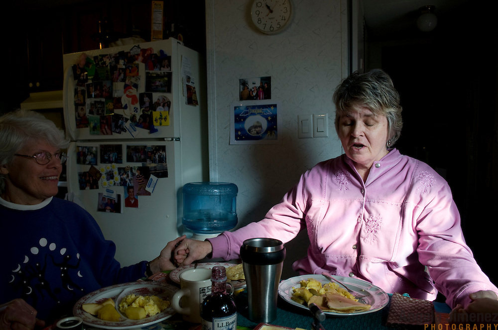 """Date: 1/09/09.Desk: STL.Slug: WOMYN.Assign ID: 30074969A..Morgana MacVicar, 61, right, says a prayer before breakfast at another resident's home at Alapine, a """"womyn's land"""" or lesbian intentional community, in rural northeast Alabama. At left is Emily Greene, 62. ..(*the exact town/location of the community cannot be revealed in the caption or article, per agreement with the subjects)..Photo by Angela Jimenez for The New York Times .photographer contact 917-586-0916"""