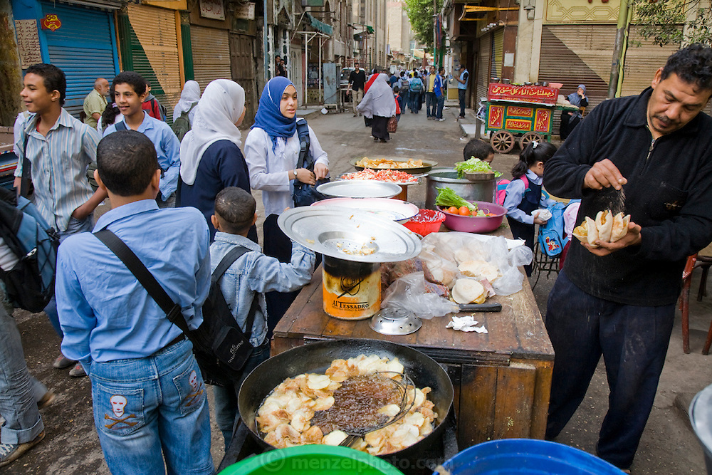 People buy deep fried snacks from an open air market at Shari Khayyamiya, a tentmakers street and market area in Cairo, Egypt.