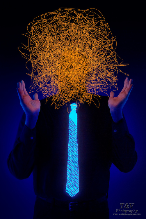 A man with a sequin tie holds his hands around a glowing scribble that takes the place of his face.Black light