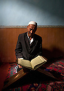 Uyghur man studying the Quran. Minfeng, Xinjiang Uyghur autonomous region, China.