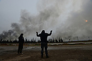 "Aleppo, Syria, December, 2012 -  Free Syrian Army rebel Capt. ABU-MAHUMUD, (L) and ABU-DIEB (R) chant ""God is Great"" as they watch Syrian army bombs land in front of them during a ferocious battle for the control of the strategically important village of Aldoreneh, which is near the airport in this city. Rebels have been trying to take the airport for weeks. (Photo by Miguel Juárez Lugo)"