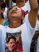 23 JUNE 2016 - MAHACHAI, SAMUT SAKHON, THAILAND: The Burmese flag is reflected in the sunglasses of a man waiting for Aung San Suu Kyi to arrive in Samut Sakhon, a province south of Bangkok. Tens of thousands of Burmese migrant workers, most employed in the Thai fishing industry, live in Samut Sakhon. Aung San Suu Kyi, the Foreign Minister and State Counsellor for the government of Myanmar (a role similar to that of Prime Minister or a head of government), is on a state visit to Thailand. Even though she and her party won the 2015 elections by a landslide, she is constitutionally prohibited from becoming the President due to a clause in the constitution as her late husband and children are foreign citizens        PHOTO BY JACK KURTZ
