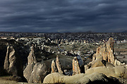 Goreme Open Air Museum, consisting of many 10th - 12th century rock-cut monasteries, refectories, churches and monks' cells, and the town of Goreme in the distance, Goreme National Park, in Nevsehir province, Cappadocia, Central Anatolia, Turkey. The churches in Goreme are carved from the soft volcanic tuff created by ash from volcanic eruptions millions of years ago. Early christians came here to flee persecution by the Romans and others settled here under the influence of early saints. This area forms part of the Goreme National Park and the Rock Sites of Cappadocia UNESCO World Heritage Site. Picture by Manuel Cohen
