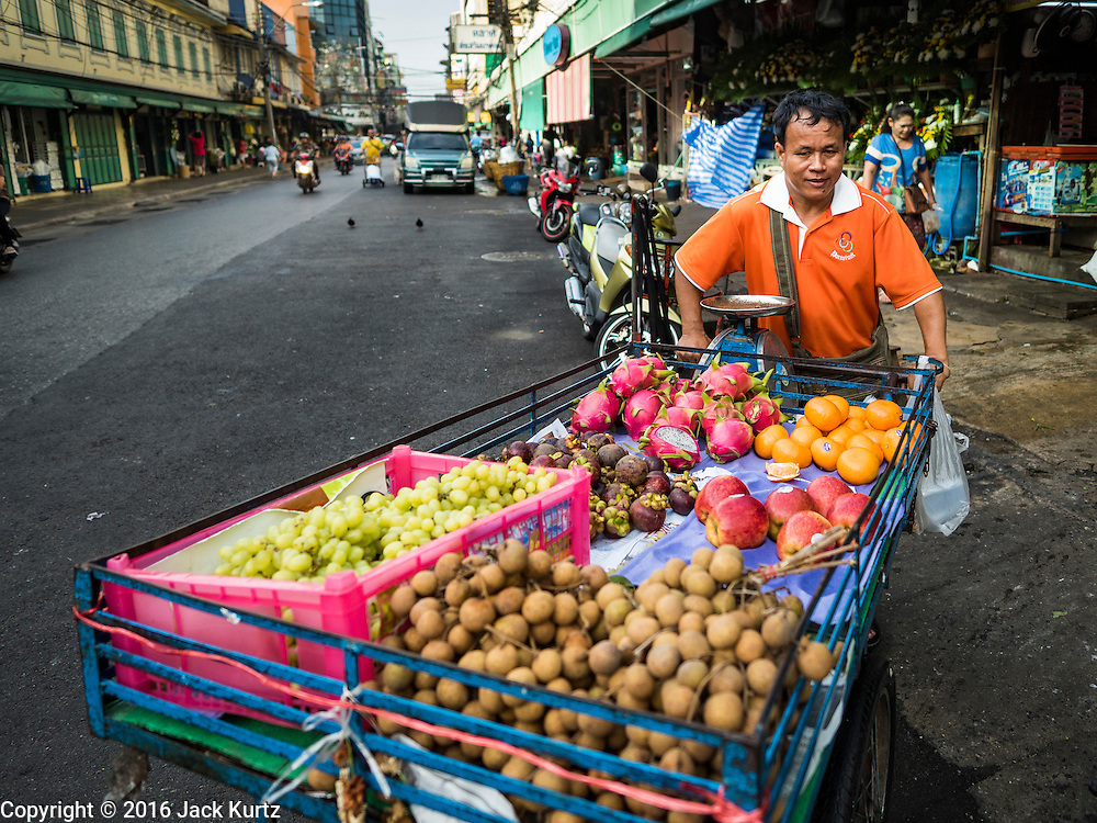 "11 AUGUST 2016 - BANGKOK, THAILAND:   A fruit seller pushes his cart past Pak Khlong Talat. Pak Khlong Talat (literally ""the market at the mouth of the canal"") is the best known flower market in Thailand. It is the largest flower market in Bangkok. Most of the shop owners in the market sell wholesale to florist shops in Bangkok or to vendors who sell flower garlands, lotus buds and other floral supplies at the entrances to temples throughout Bangkok. There is also a fruit and produce market which specializes in fresh vegetables and fruit on the site. It is one of Bangkok's busiest markets and has become a popular tourist attraction.          PHOTO BY JACK KURTZ"