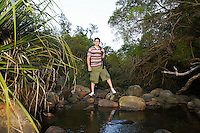 Young Hiker Standing by Creek