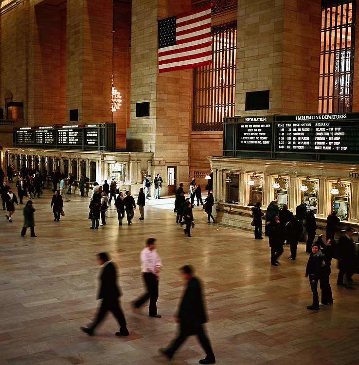 People walking past departure boards and ticket booths, Grand Central Terminal, New York