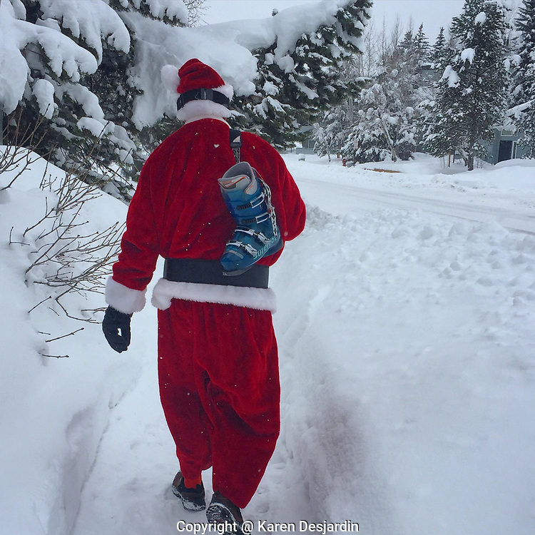 Santa carries his ski boots as he walks to the ski slope on Christmas Day in Steamboat Springs, Colorado.