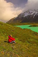 Female hiker enjoying the view of Lake Nordenskjold (Paine Grande in background), Torres del Paine National Park, Patagonia, Chile