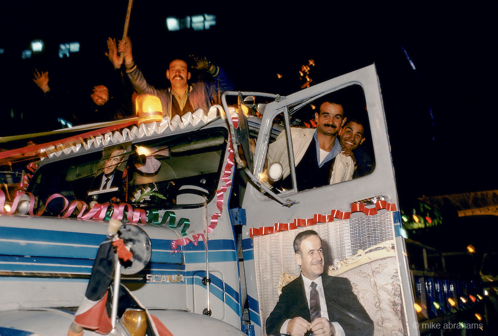 'PERSONALITY CULT OF ASSAD', MEN RIDING IN & ON CAB OF TRUCK WITH PHOTO POSTER OF ASSAD ON THE DOOR DURING THE REFERENDUM CAMPAIGN, DAMASCUS, DECEMBER 1991.