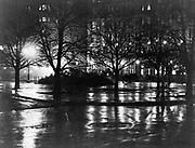 New York City street on a wet winter night lit by gas street lights, c1885.