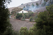 Multiple fire departments, including Milpitas Fire Department, Spring Valley Fire Department, and Cal Fire, work to contain and extinguish a structure fire at the 3000 block of Calaveras Road near Spring Valley Golf Course in Milpitas, California, on February 10, 2014. (Stan Olszewski/SOSKIphoto)