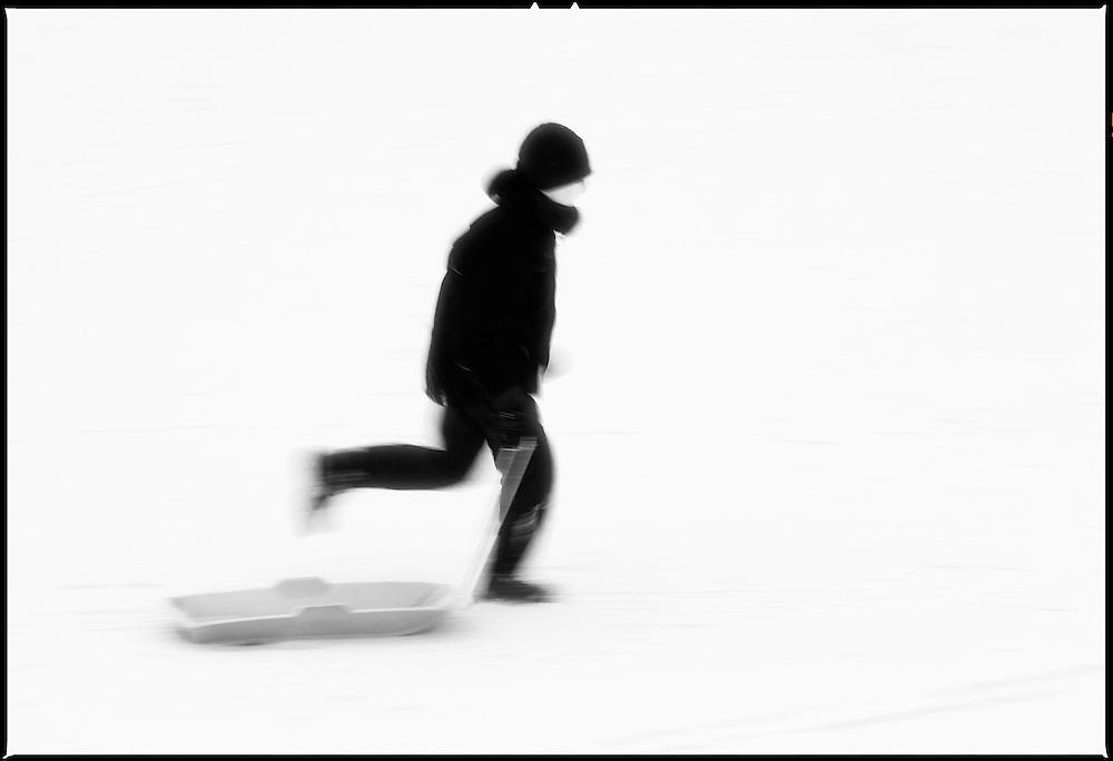 Boy running with sledge, Scotland