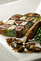 Venison and Foie gras Terrine, parsley salad the side, white plate on a gray marble table, Close up