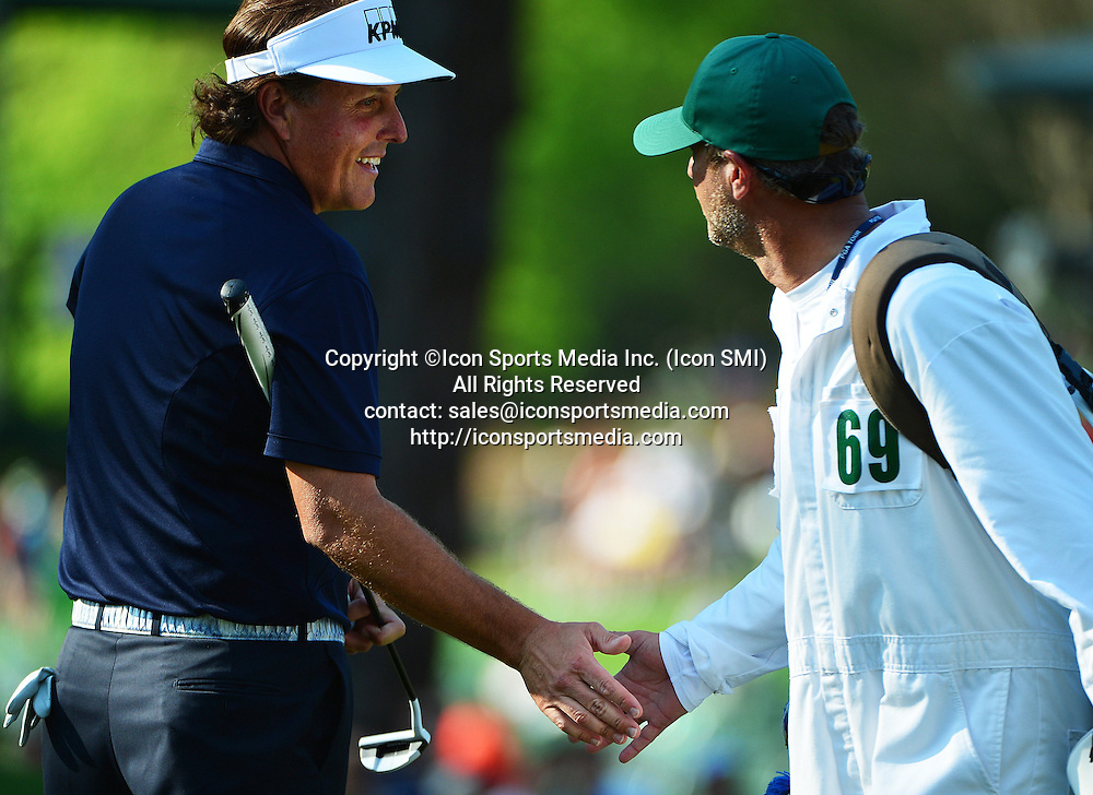April 9, 2013 - Augusta, Georgia, U.S. - Phil Mickelson, left, shakes hands with Lance Bennett, Matt Kuchar's caddie, on the sixth green during the second practice round for the 2013 Masters Tournament at Augusta National Golf Club on Tuesday, April 9, 2013, in Augusta, Ga.
