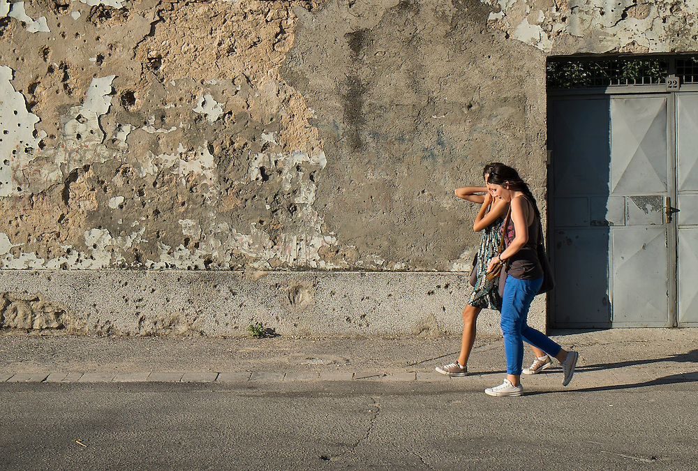 MOSTAR, BOSNIA AND HERZEGOVINA - JUNE 28:  Two women walk in front of a concrete wall damaged by bulletts from the 1993 war is seen on June 28, 2013 in Mostar, Bosnia and Herzegovina. The Siege of Mostar reached its peak and more cruent time during 1993. Initially, it involved the Croatian Defence Council (HVO) and the 4th Corps of the ARBiH fighting against the Yugoslav People's Army (JNA) later Croats and Muslim Bosnian began to fight amongst each other, it ended with Bosnia and Herzegovina declaring independence from Yugoslavia.  (Photo by Marco Secchi/Getty Images)
