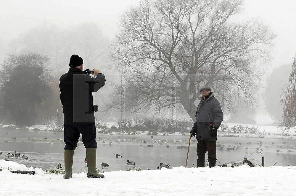 © under license to London News Pictures 06.12.2010 Two elderly men pose for photographs of each other in the snow at Footscray Lake, Kent, today (Mon).  Forecasters say Britain's 'Big freeze' is set to continue throughout The week. Picture credit should read Grant Falvey/London News Pictures.