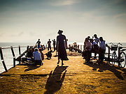 10 NOVEMBER 2014 - SITTWE, MYANMAR: People on one of the piers in Sittwe. Small boats tie up on this pier to bring in bananas and other fruit and land fish caught in the nearby Bay of Bengal. Sittwe is a small town in the Myanmar state of Rakhine, on the Bay of Bengal.    PHOTO BY JACK KURTZ