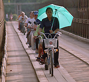 A woman with an umbrella leads a convoy, albeit slowly, of bikes across a bridge in Luang Prabang, Laos.